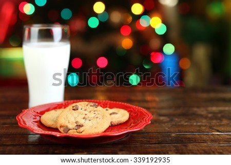 Cookies and milk for Santa Claus in front of a Christmas tree - stock photo