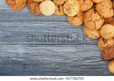 Cookies and sweet biscuits at blue wood, background with copy space. Oatmeal and chocolate drops cookies border, dessert for tea. - stock photo