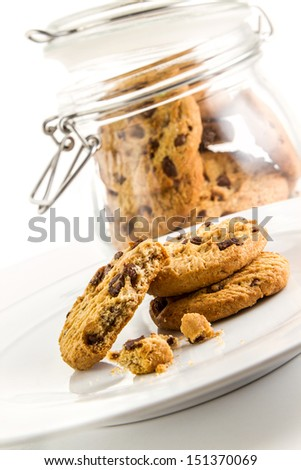 Cookies arranged on a white plate with cookies in a jar on background - stock photo