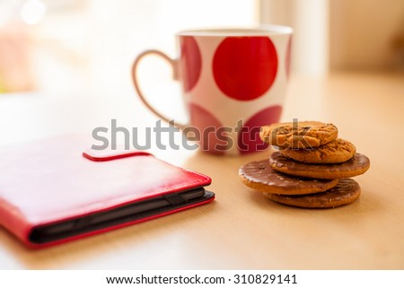 Cookies Biscuits Pile Cup Drink Tea Tablet e-reader Natural Light - stock photo