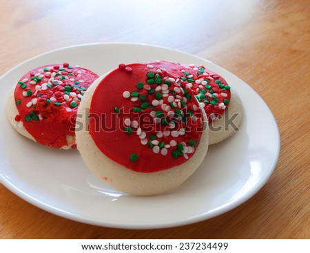 Cookies decorated with red frosting and sprinkles for Christmas - stock photo