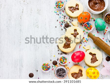 Cookies easter bunny, colorful sprinkling, chocolate, decorative eggs top view. Food art idea for kids. Easter holiday baking background - stock photo