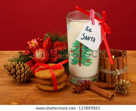 Cookies for Santa: Conceptual image of ginger cookies, milk and christmas decoration on red background - stock photo