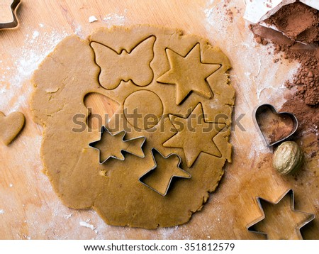 Cookies forms and gingerbread dough on wooden pastry board