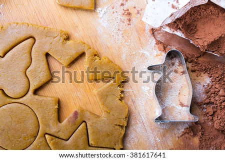 Cookies forms and gingerbread dough on wooden pastry board - stock photo