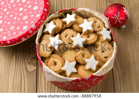 Cookies in a tin and christmas ball on a wooden background - stock photo