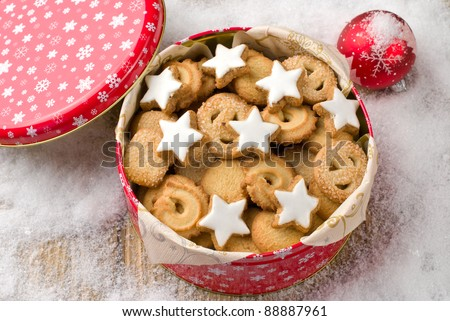 Cookies in a tin and christmas ball on a wooden background covered with snow - stock photo