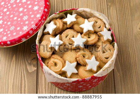 Cookies in a tin on a wooden background - stock photo