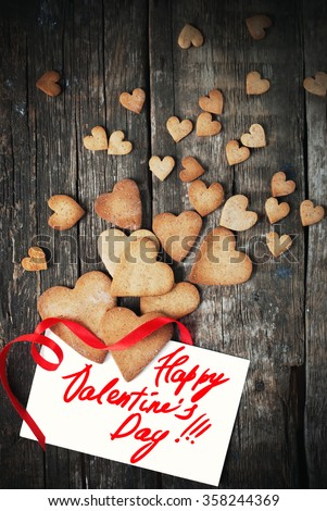 Cookies in Shape of Hearts for Valentine's Day. Cards with Pastry, Message Isolated on White and Red Ribbon on Wooden Table. Valentines theme - stock photo