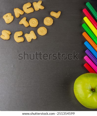 Cookies in the form of letters lined inscription back to school. On the blackboard with colored pens and fresh green apple. Selective focus. - stock photo