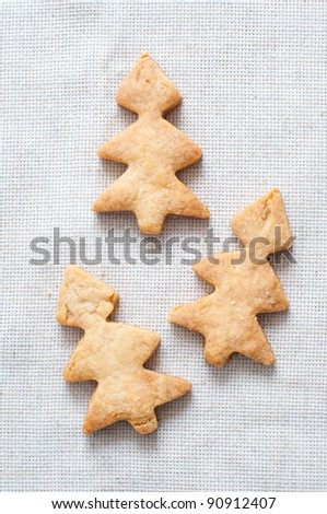 Cookies in the shape of Christmas trees on the tablecloth