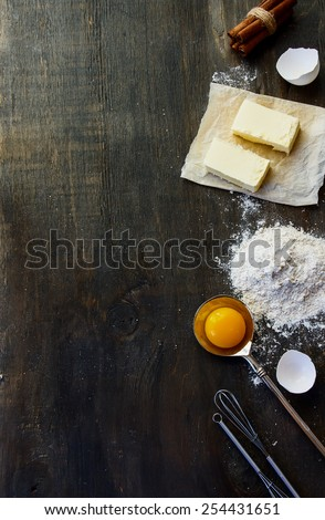 Cookies ingredients - flour, sugar, egg, butter on vintage wood table. Top view. Rustic background with free text space. - stock photo