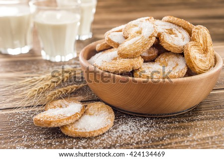 cookies on the table sprinkled with sugar and milk in a glass - stock photo