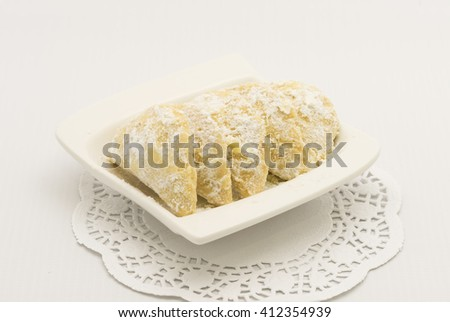 Cookies rolled in powdered sugar on white plate and paper doilies. Made of buttery, shortbread style dough with ground nut fillings.   - stock photo