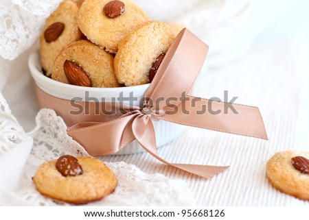 Cookies with almond in the center, dish decorated with ribbon and lace