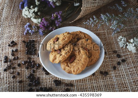 cookies with almonds and raisins on a white plate. coffee bean, flowers and bamboo net background, tasty - stock photo