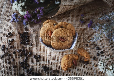 cookies with almonds and raisins on cup cake. coffee bean, flowers and bamboo net background, tasty - stock photo