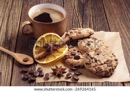 Cookies with chocolate and cup of black coffee on dark wooden table - stock photo