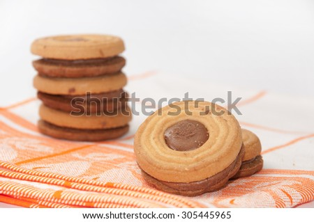 Cookies with chocolate cream on a kitchen tablecloth. - stock photo