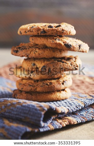 Cookies with chocolate crumbs on ornament napkin against blurred background, close up - stock photo