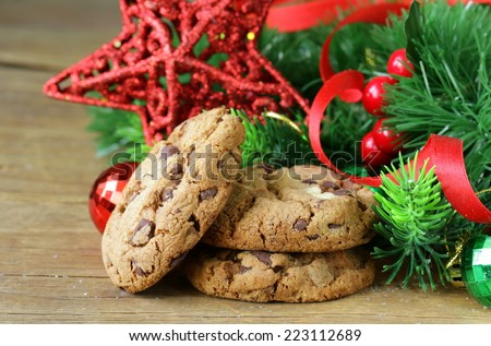 cookies with chocolate on a wooden background with Christmas tree branches and decorations - stock photo