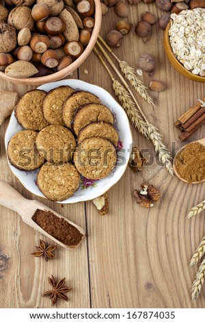 Cookies with Cocoa, Flour, Spices and Nuts on Wooden Background