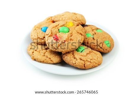 Cookies with colorful candy on plate isolated on white - stock photo