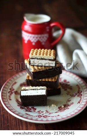 Cookies with marshmallow and dark chocolate frosting on a plate, selective focus - stock photo