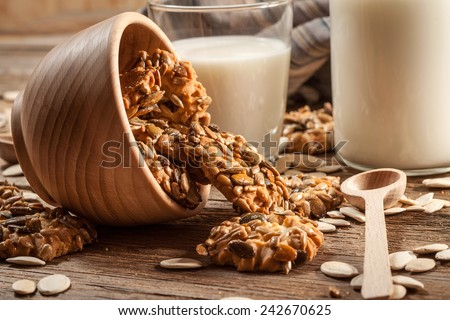 Cookies with pumpkin seeds and cinnamon with a glass of milk on a wooden background. Selective focus. - stock photo