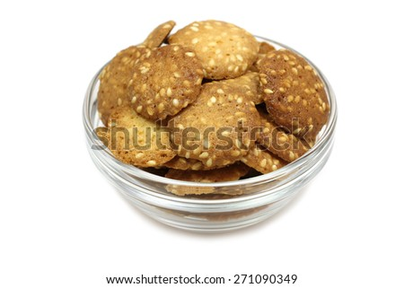 cookies with sesame seeds in a glass cup on a white background - stock photo