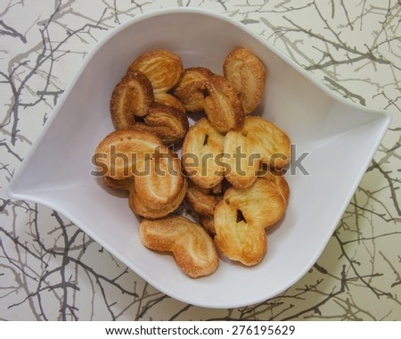 Cookies with sugar in the plate on the kitchen table - stock photo