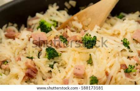 Cooking a pan of hash brown potatoes with ham, broccoli and onions