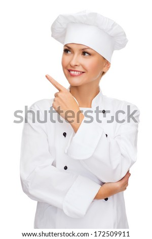 cooking, advertisement and food concept - smiling female chef, cook or baker pointing finger to something - stock photo
