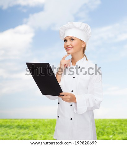 cooking, advertisement and food concept - smiling female chef, cook or baker with blank black menu paper - stock photo