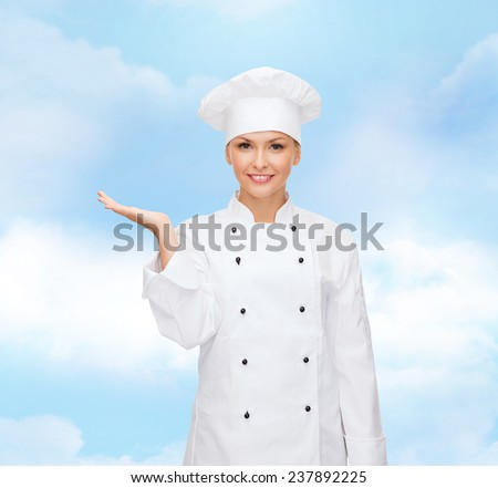 cooking, advertisement and people concept - smiling female chef, cook or baker holding something on palm of hand over blue cloudy sky background - stock photo