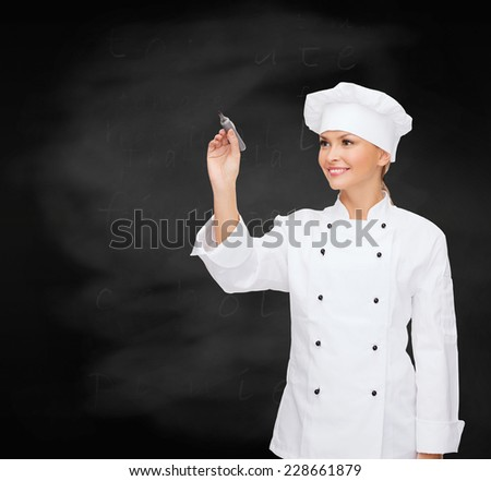cooking, advertisement and people concept - smiling female chef, cook or baker with marker writing something on air over blackboard background - stock photo