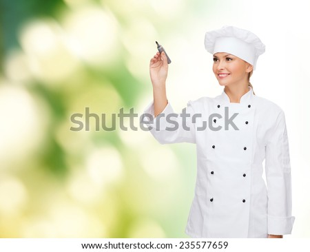 cooking, advertisement and people concept - smiling female chef, cook or baker with marker writing something on air over green background - stock photo