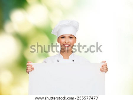 cooking, advertisement and people concept - smiling female chef, cook or baker with white blank board over green background - stock photo
