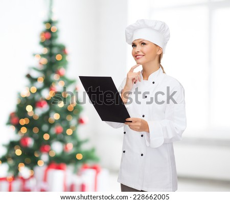 cooking, advertisement, holidays and people concept - smiling female chef, cook or baker with blank black menu paper thinking over living room and christmas tree background - stock photo