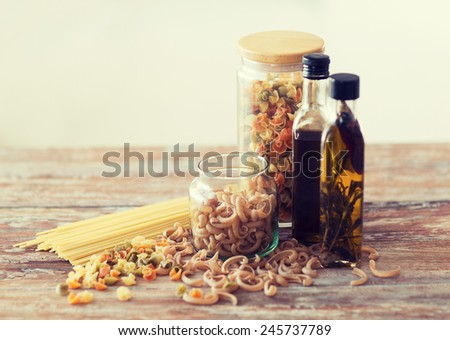 cooking and food concept - close up of two olive oil bottles and pasta in jars - stock photo