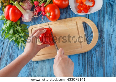 cooking and home concept - close up of female hand cutting tomato on cutting board with sharp knife - stock photo