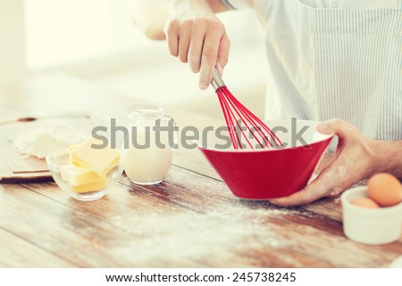 cooking and home concept - close up of male hand whisking something in a bowl - stock photo