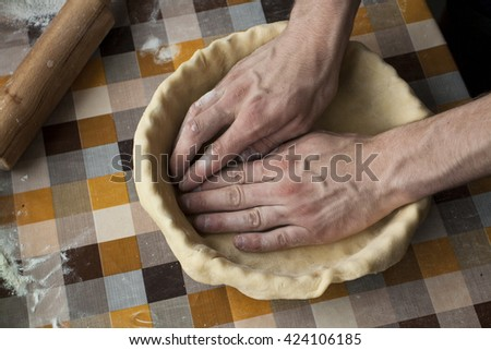 Cooking and home concept - close up of male hands kneading dough on a background in cell - stock photo