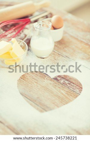cooking and love concept - close up of heart of flour on wooden table at home - stock photo