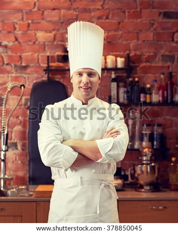 cooking and people concept - happy male chef cook with crossed hands in restaurant kitchen - stock photo