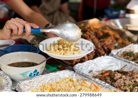 cooking, asian kitchen, sale and food concept - close up of hands with plate, spoon and wok at street market - stock photo