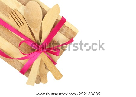 Cooking background - cutlery on cutting board tied with ribbon isolated on white background - stock photo