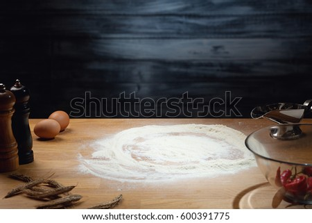 Cooking background, flour on wooden table. Low key shot, light on flour, some ingredients around on the table. Copy space.
