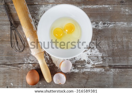 Cooking background with eggs, raw eggs in a dish, eggshells, flour, rolling pin and whisk on a wooden background. - stock photo