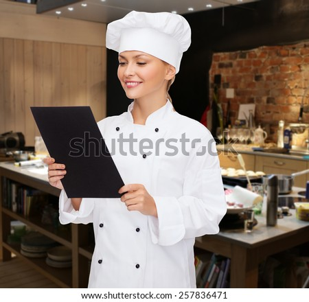 cooking, bakery, people, advertisement and food concept - smiling female chef cook or baker with blank black menu paper over restaurant kitchen background - stock photo